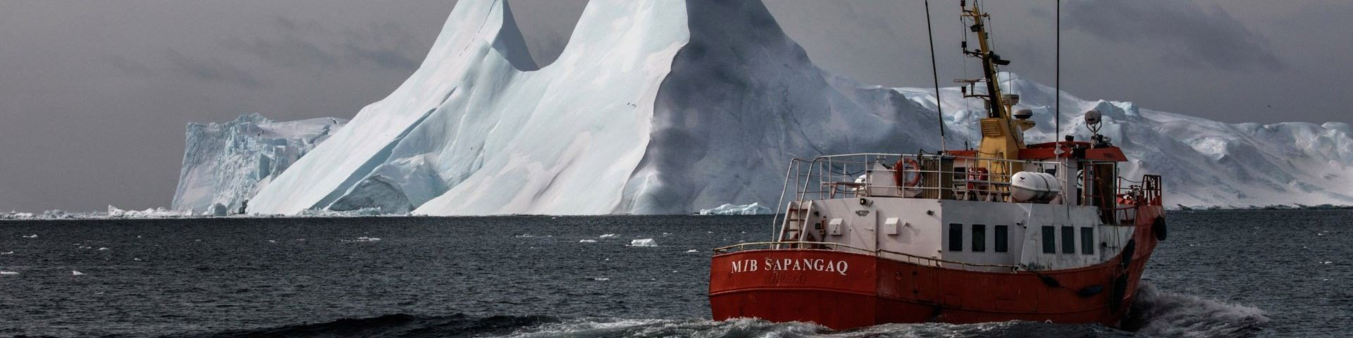 A red boat sails on cold grey water, with a huge floating iceberg behind it.